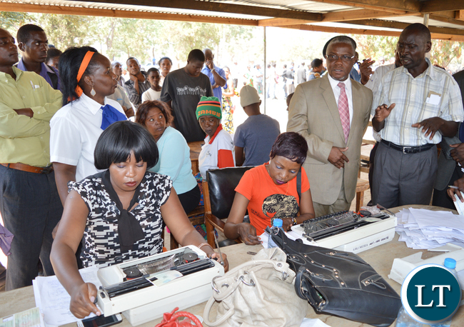 SOUTHERN Province Minister Nathaniel Mubukwanu (in a suit) with provincial registrar Mwanda Shingululu (right) inspect the mobile issuance of National Registration Cards (NRCs) in Choma
