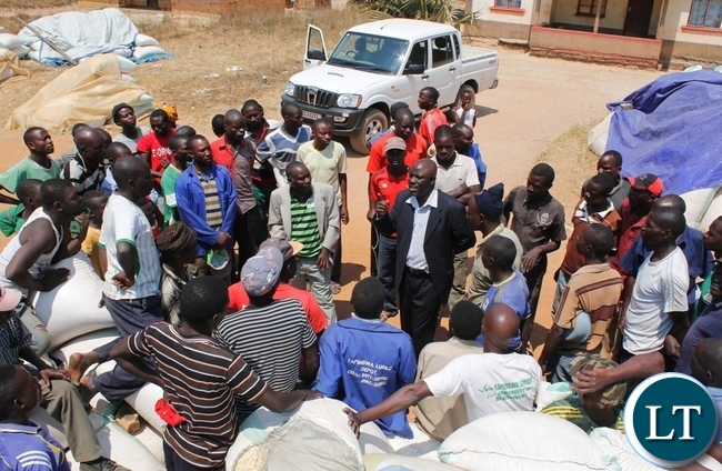 ut-going Acting Mbala District Commissioner, Felix Mungaila thronged by farmers when he visited Mambwe Mission satellite depot to check on the progress of the marketing season