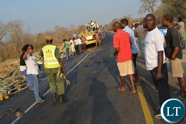 Kazungula District Commissioner Pascalina Musokotwane (in white t-shirt) and police officers trying to control residents from looting the cooking oil which dropped on the roadside after a truck overturned