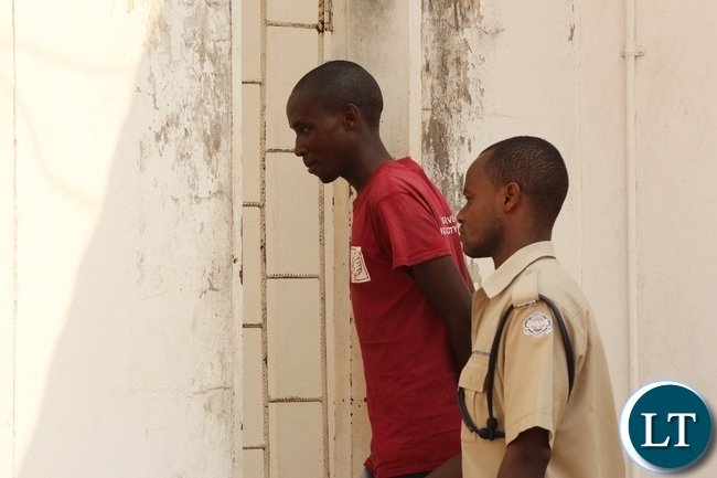 Police escorts Hatch Bril (l) back to his holding cell after a court trial facing sodomy charges in Mongu yesterday. The case has been adjourned to October 14, 2015.