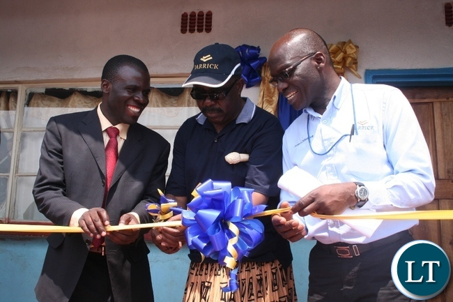 Chief Mumena (m) with Solwezi acting district commissioner Chipawa Chipawa (l) and Lumwana mining company community relations superintendent Harrington Kanema (r) cutting a ribbon during the official handover of the three teachers' houses constructed by the mining firm at a total cost of K357,000 at Mwajimambwe school at Mutanda