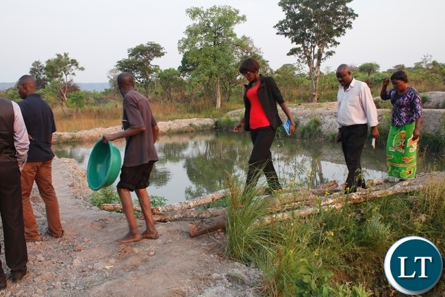 Mbala district administrative officer, Felix Mungaila with SUN programme Corrdinator and Assistant Fisheries technician checking the fish ponds at Chitusa fish farming group in Agriculture camp