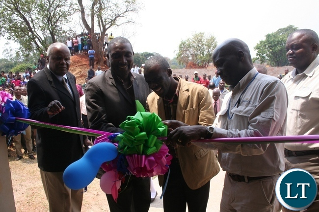 Acting Solwezi district commissioner Chipawa Chipawa (m) with Lumwana mine company community relations superintendent Harrington Kanema (second right) and Meheba secondary school headteacher James Kawang'u (l) and provincial principal education standards officer Brainley Malambo cutting a ribbon during the official handover of a 1 x3 science laboratory to government constructed by the Lumwana Community Fund at a total cost of K782,000 in Kalumbila in North-Western province