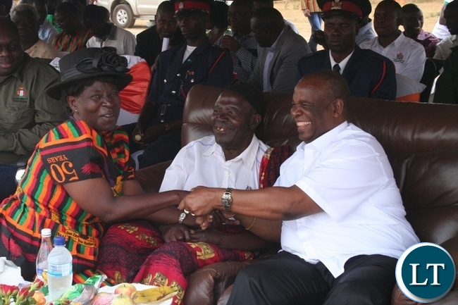 Higher education minister Dr Michael Kaingu (r) shares a light moment with former health minister and also former member of the central committee Allina Nyikosa (l) during the 51st Zambia 's Independence celebrations at Solwezi stadium in Solwezi on Saturday as North-Western province freedom fighters chairman Bwanga Wisamba (m ) looks on