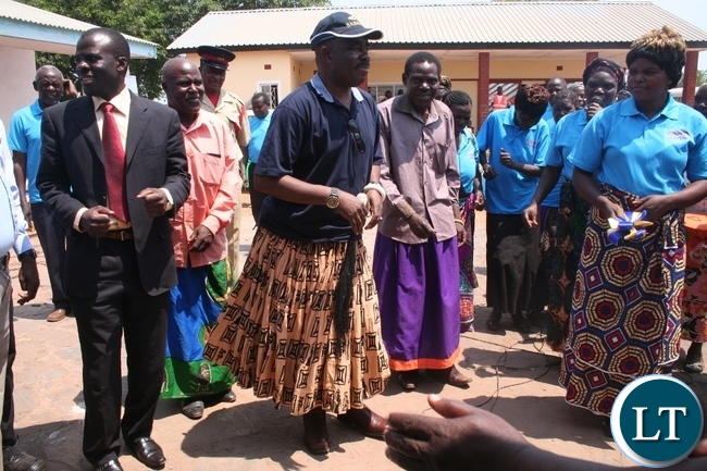 Solwezi acting district commissioner Chipawa Chipawa (l) with chief Mumena (in a cap) dancing to the Mukumbi Ibaloli culture song on Thursday during the official handover of Mukamena Multipurpose cooperative centre which has been constructed by Lumwana mining company at Mutanda at a total cost of K240,000.
