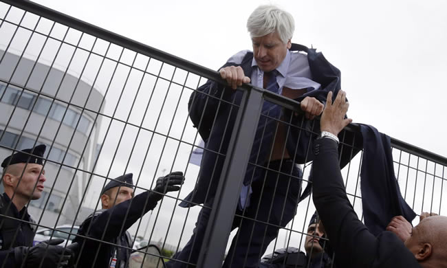 Pierre Plissonnier, vice-president of Air France at Orly airport in Paris, is helped by police to escape the protesters. Photograph: Kenzo Tribouillard/AFP/Getty Images