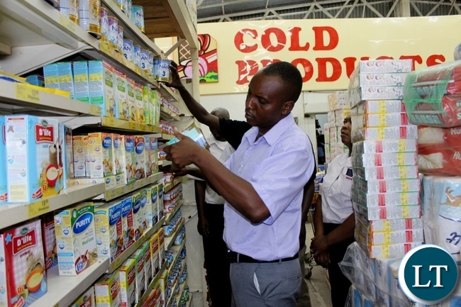 Western Provincial Competition and Consumer Protection Commission (CCPC) Investigator Mutemwa Nakambowa (c) checking the expiring date on baby products in Shoprite during an Inspection and Sensitization Tour to Traders to observe the CCPC Act in Mongu