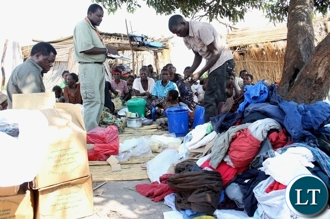 Mongu District Commissioner Susiku Kamona (l) and DMMU District Secretary Matakala Mbangweta (c) listing clothes to be given to disaster victims of a firestorm which burnt the entire Imuba Village to ashes in Lower Katongo area in Mongu.