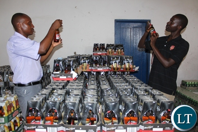 Ministery of Health Environmental Health Technologist Nanzaluka Hantontola (r) and Western Provincial Competition and Consumer Protection Commission (CCPC) Investigator Mutemwa Nakambowa (l) checking expiring dates on Zambian Breweries beverages at Mongu Depot during an Inspection and Sensitization Tour to Traders to observe the CCPC Act