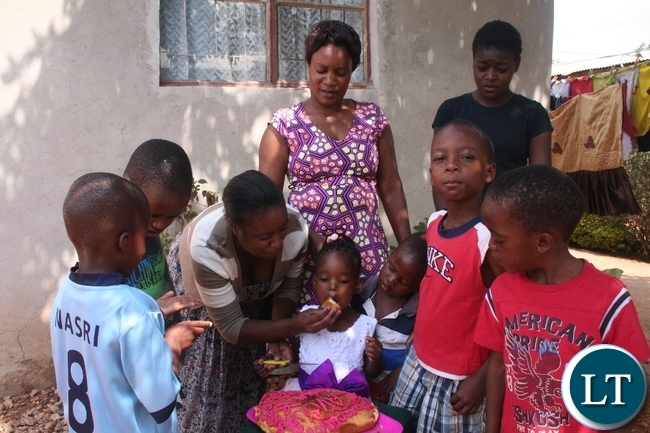 The Bible in Psalms 127: 3 says Children are a gift from GOD; and such they are a real blessing. Above, Faviour Kaoma (in a white dress) being given a cake by her auntie Jessie Swetu (l) as Faviour's mother, Christine Kaoma (standing left) looks on during Faviour's third birthday celebrations on Sunday in Solwezi