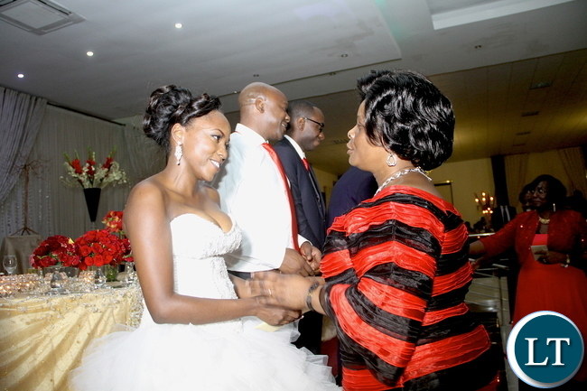 First Lady Esther Lungu congratulates PF Chifubu member of Parliament Susan Kawandami's daughter Chinyimba who got married to former Zambia Army commander Benjamin Mibenge's son Bweupe (in a white shirt) at ZAF Chamba Valley Officers' Mess in Lusaka on Saturday, November 14,2015 -Picture by THOMAS NSAMA
