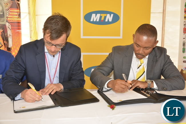 MTN Zambia CEO Charles Molapisi and Total Zambia Managing Director Damien Ricour-Dumas signing the MTN Mobile Money partnership agreement at Parkway Service Station on Kafue Road