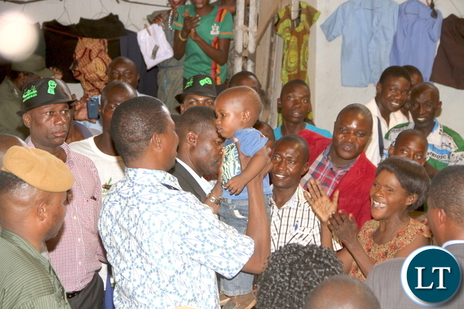 President Lungu lifts a Baby during a tour of Kalulushi Market on the Copperbelt on Monday, November 2,2015 -Pictures by THOMAS NSAMA