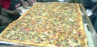 Pizza Hut workers unveiling the largest pizza ever made in Zambia