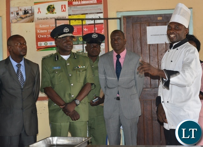 The chef instructor for Lusaka youth resource center Mr. Prince Kampanoa explains to the Acting Permanent Secretary Ministry of Youth Sport and child Development Mr. Alfonso Banda (l) next the deputy inspector general of police Mr. Engine Sibote (c) how they operates at the center during the graduation ceremony for the Lusaka youth resource center