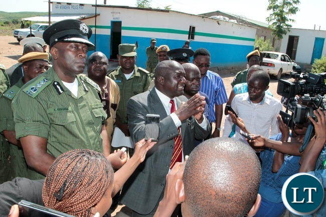 Kafue District Commissioner Ngoni Moyo (in a suit) who is flanked by Inspector General of Police Kakoma Kanganja (l) speaking to residents shortly after inspecting Mtendere Police Post in Chawama Compound Kafue that was damaged by people in the area