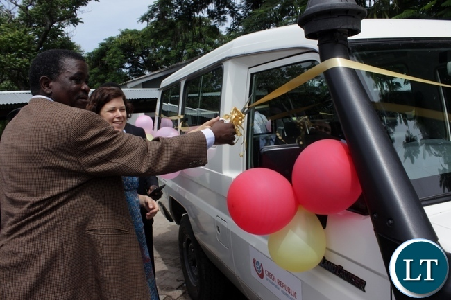 Western Province Permanent Secretary Mwangala Liomba (l) cuts the ribbon together with Caritas Czech Republic Head of Mission in Zambia Tea Tihounova (c) during a donation of a Toyota Land Cruiser worth $53,400 from Caritas Czech Republic to Lewanika School of Nursing and Midwifery in Mongu