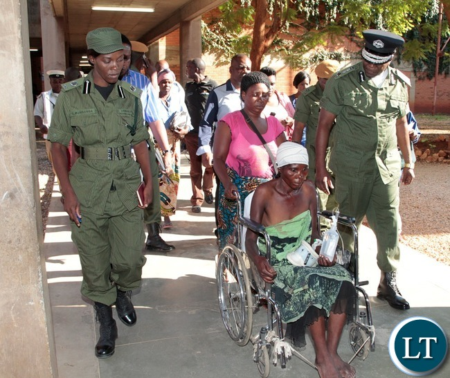 Inspector General of Police Kakoma Kanganja (r) and Police Public Relation Officer Charity Munganga Chanda (l) escort Irene Kaluba at University Teaching Hospital who was hit by a Police car in Kafue
