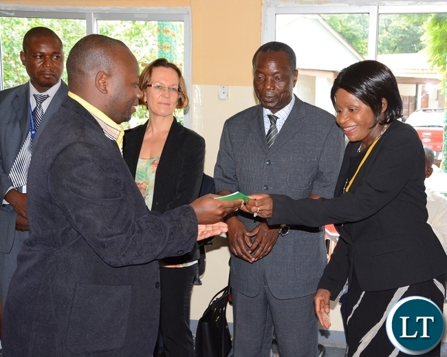 Ministry of Home Affairs Permanent Secretary Elwyn Chomba gives Alain-Jules Kayihura resident permit whilst her Deputy Permanent Secretary Willies Manjimela (c) looks on during the launch of Integration for Former Rwandan Refugees at the Commissioner for Refugees Conference room