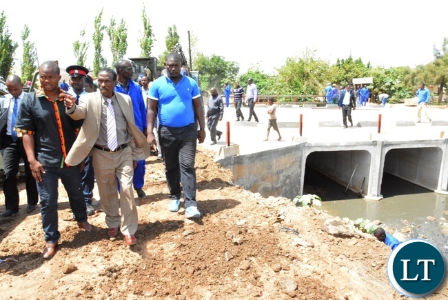Deputy Minister in the office of the Vice President Lawrance Sichalwe (centre in a suit) inspects Chunga bridge in Matero