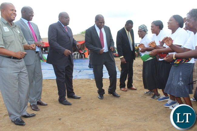 Monze District Commssioner Mr. Cyprian Hamanyanga ( right), Deputy Minister of Health Dr Chitalu Chilufya( second from right) and other senior health officials join in dancing during the joyous occasion to mark the commissioning of Muunyumabisi Health Post in Monze District