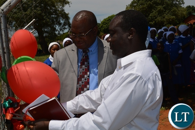 SDA South Zambia Conference president Maxwell Muvwimi (left) and Livingstone district planning officer Elvis Siyauya (right) cuts a ribbon during the official opening of Victoria Falls Adventist Primary School in Livingstone