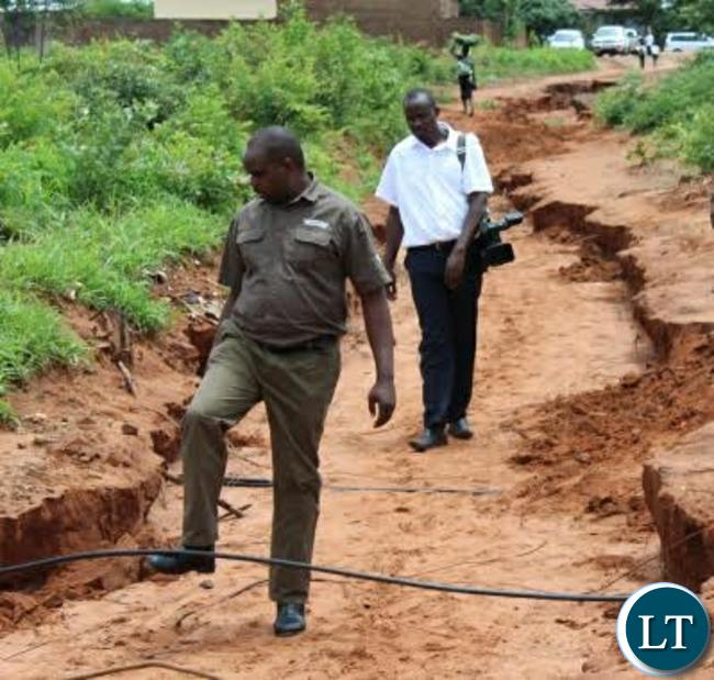 Livingstone District Commissioner Omar Munsanje inspects some water pipes that have been brought to the surface following heavy rains experienced in Livingstone