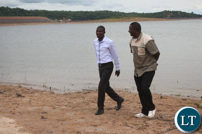 Ithezi Thezi member of parliament who is also Deputy Minister of Agriculture Greyford Monde walks on the Bank of Ithezi thezi Dam with Zesco spokesperson Henry Kapata in Ithezi Thezi.