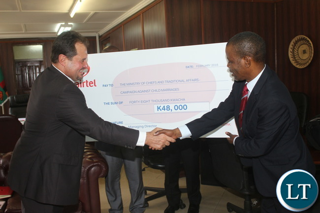 """The Minister of Chiefs and Traditional Affairs Dr. Joseph Katema receives Airtel Zambia Plc Peter Correia that handed over a cheque worth of K 48 Thousand towards the fight of """"Child Marriages"""" at his office"""