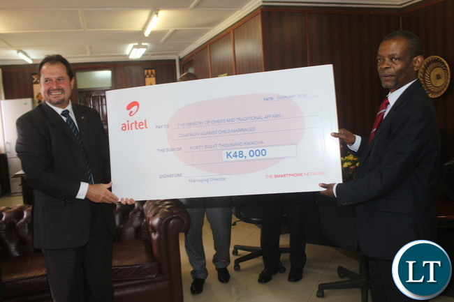 "The Minister of Chiefs and Traditional Affairs Dr. Joseph Katema receives Airtel Zambia Plc Peter Correia that handed over a cheque worth of K 48 Thousand towards the fight of ""Child Marriages"" at his office"