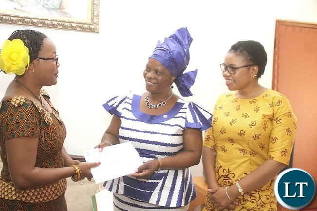 Mrs. Mwamba presenting details of the donation to Esther Lungu Foundation Trust (ELFT) Founder, the First Lady Mrs. Esther Lungu at State House in Lusaka on 4th March, 2016. Looking on is ELFT Board Member, Ms. Bernadette Deka.