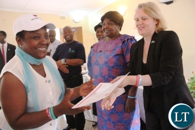 UN Resident Coordinator Janet Rogan presents a certificate of attendance to Kasama Administrative Officer Beauty Namukoko at Sinamu lodge in Kasama shortly after the launch of the HEFORSHE campaign today. Looking on is Gender Deputy Minister Dorothy Kazunga and Northern PS Hlobotha Nkunika.