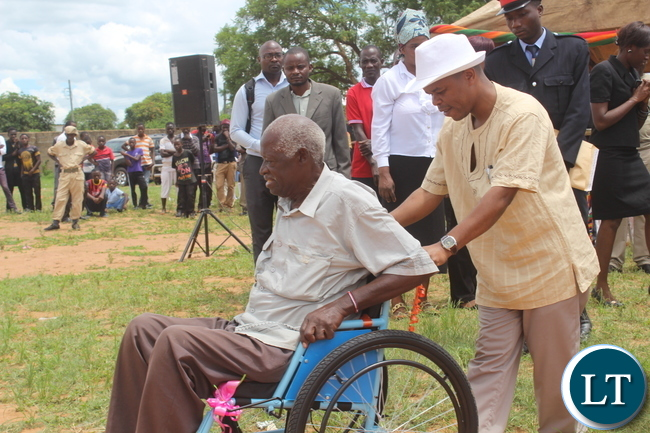 eputy Minister of Education Mr. Sydney Mushanga( left in white hat) helps 70 year-old Simon Hapenga (in wheel chair) after Monze District Youth Day Organisaing Committee donated a  wheel chair worth K2,220.00 to him during Youth Day celebrations in Monze