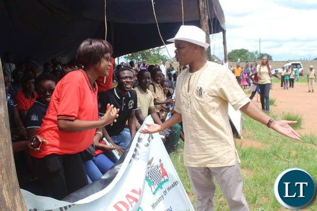 Deputy Minister of Eduaction (right in white hat) who was the guest of honour challenges Monze youths to dance with him  during  the Youth Day Celebrations