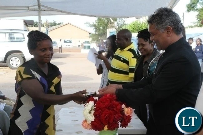 Agriculture Minister Given Lubinda(r) giving a present to one of the beneficiaries of Divine Mercy Home Care Margaret Katenga(l) for making it to grade 8 during the donation in Chilenje