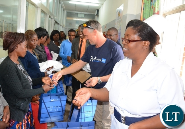 Raddison Blu Hotel General Manager Marius Wolmarans (2nr) and AO5 ward sister in-charge Noreen Choopa give the donation of towels and food staffs to the mother of the patients in ward AO5 at UTH