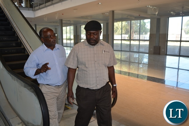 State House Special Assistant for Project Monitoring and Implementation Lucky Mulusa (right) with Ndilila Associates director Francis Ndilila (left) leaving the elevators during a tour of International Bus Terminus currently under construction in Livingstone