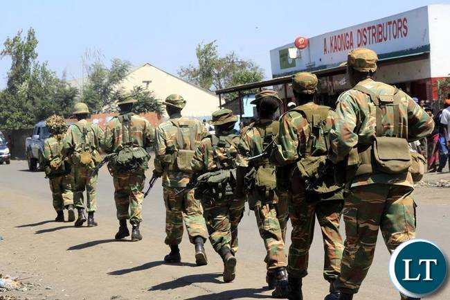 Soldiers from the Zambia Army patrolling compunds in Lusaka