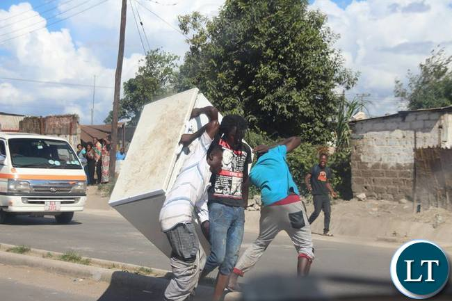 Some guys carrying a fridge believed to be looted along   Zingalume - Matero road.