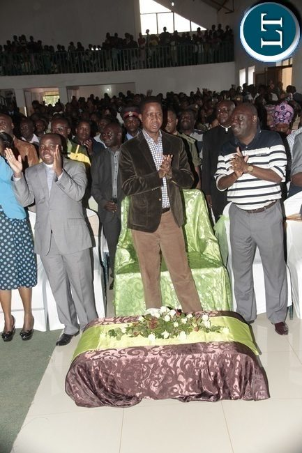 President Edgar Lungu singing a song Reverend Sams Kafunda on his right and PF secretary General Davies Chama Left When he attended a church service at Blessed of Hope Church