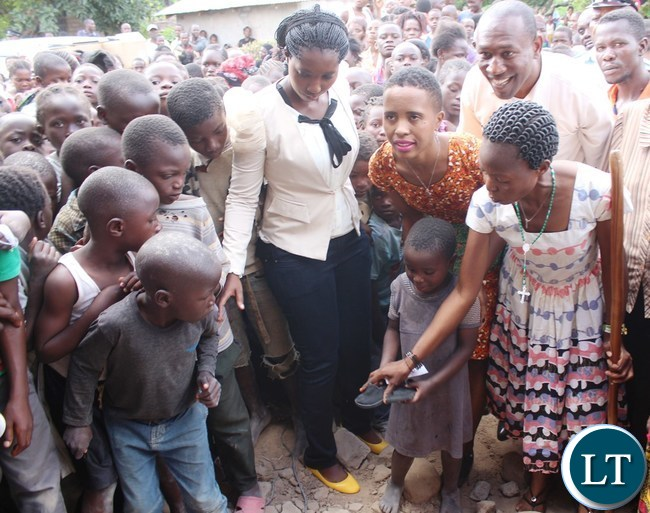 Ubulayo Charity organization founder Tasila Lungu with Hildah Nkole 7, a pupil at Chiba Community School in Kasama district today after she made a donation of shoes to over 200 vulnerable and orphaned pupils at the school. Looking on is Kasama District Commissioner Kelly Kashiwa and School Head Catherine Bwalya (walking stick)