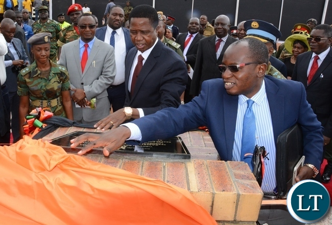 Special Assistant for Press and Public Relation for the President Amos Chanda helps President Edgar Lungu to unveil the plaque at official ground breaking ceremony of ZAF twin Palm Public Private Partnership Project on Support Social Amenities and Commercial Facilities whilst Lt Muwindwa Liusha looks on