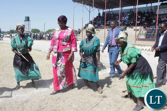 Community Development Minister Emerine Kabanshi (c) dance with Yuka Cultural Group women during the 2016 Labour Day Celebrations at Mongu stadium