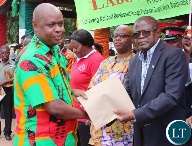 Mines and Mineral resources Minister Christopher Yaluma presents an ward to Morries Kamenda at President's Park in Kasama today during labour day celebrations. looking on is norther PS Hlobotha Nkunika.