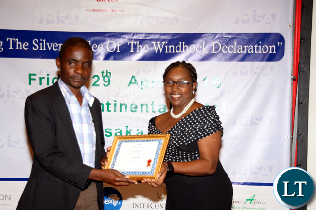 MUVI TV's Kennedy Phiri (l)receives an ward for best business reporting-TV from MIZambia chairperson Hellen Mwale during the 2016 MISA Zambia annual awards in Lusaka on April 29, 2016.