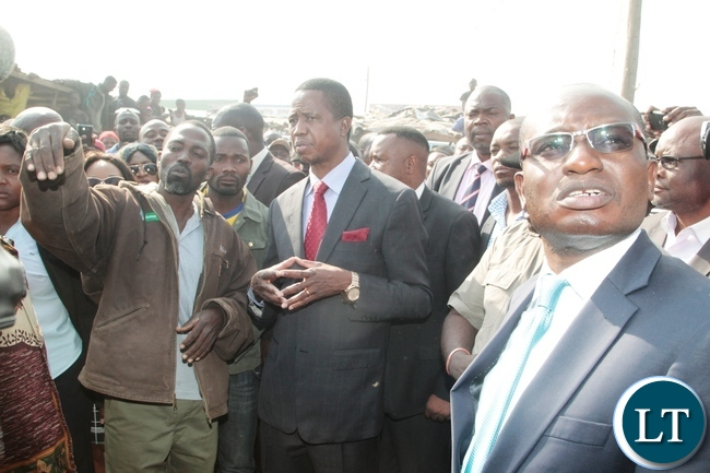 Shop keeper Special Sinjese explains to President Edgar Lungu on the burnt down shops at Bauleni Market