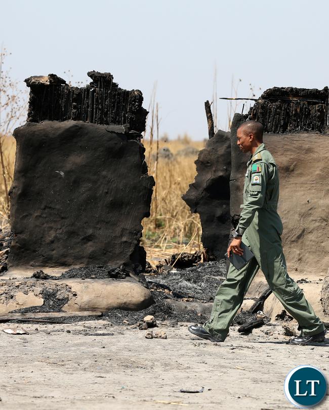 ZAF Pilot walking through burnt Chikwato Village