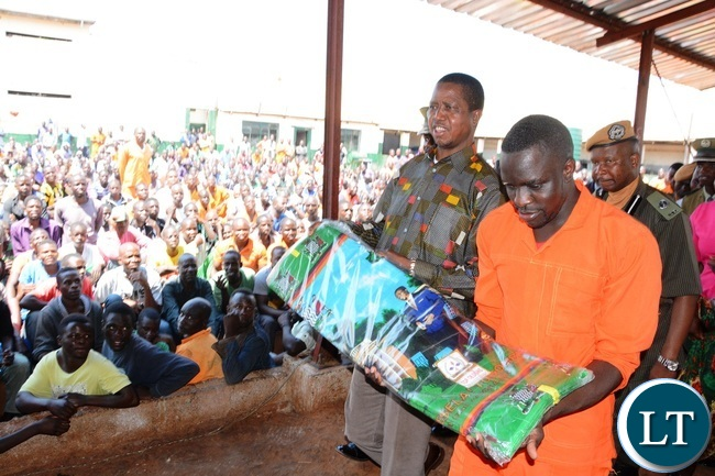 President Edgar Lungu handing over chitenge materials to inmates during the donated goods shortly before handing them over