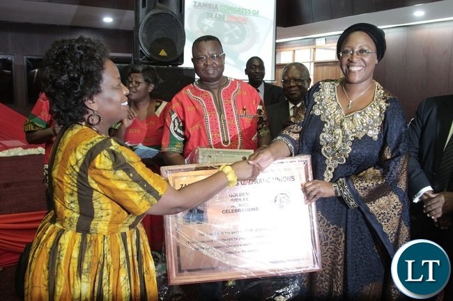 Minister of Labour Joyce Nonde presents the award to Dr. Christine Kaseba on behalf of her late Husband Micheal Sata (Post-Humously) whilst ZCTU President Chishimba Nkole looks on during Zambia Congress Trade Union Golden jubilee award Celebration at Mulungushi Conference Center