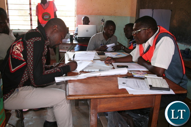 PATRIOTIC candidate for Kalumbila council chairperson Slavian Bulaya (r ) filling in his nomination papers as returning officer Geoffrey Kaleji looks on at Mwajimambwe primary school on Thursday in Kalumbila district.
